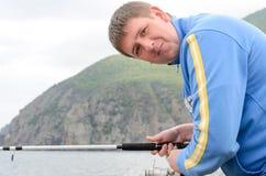 Fisherman fishing at the coast Royalty Free Stock Image