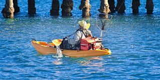 Fisherman with fishing gear paddling a Kayak. Fisherman with fishing gear paddling a Kayak in blue water near a jetty. Coffs Harbour, New South Wales, Australia Royalty Free Stock Photos