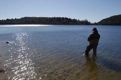 Fisherman fishing on a lake. At sunset Stock Images