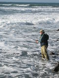 Fisherman. A fisherman fishing with lures in the coast of Sardinia Stock Photography