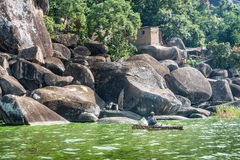 Fisherman fishing near rocks and houses on the shore of Lake Vic Royalty Free Stock Images
