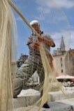 Fisherman and a fishing net. Fisherman kniting a fishing net in a small town Rovinj in Croatia Stock Image