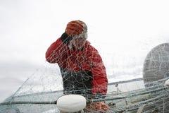 Fisherman With Fishing Net On boat. Fisherman detangling fishing net on boat Royalty Free Stock Image