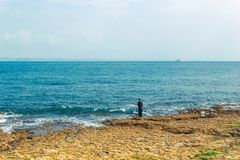 Fisherman fishing in Oeiras with lighthouse on the horizon, Port royalty free stock images