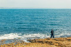 Fisherman fishing in Oeiras, Portugal. Deep blue ocean and rocky beach landscape, with shallow waves. Using a fishing rod royalty free stock image
