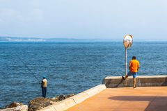 Fisherman fishing in Oeiras, Portugal. Deep blue ocean and rocky beach landscape, with shallow waves. Using a fishing rod. Orange shirt, street mirror royalty free stock photo