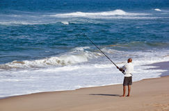 Fisherman Fishing Off Blue Lagoon Beach in Early Morning Stock Image
