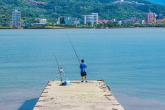 Fisherman fishing on a pier. In Taiwan Royalty Free Stock Photos
