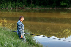 Fisherman fishing relax vacation fish nature summer green lake r. Iver water fishing rod spinning man leisure hobby men`s leisure outdoor freedom Stock Photography
