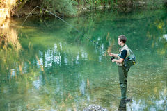 A fisherman fishing on a river Stock Photos