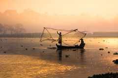 Fisherman fishing from river Stock Images