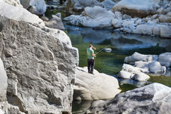 Fisherman fishing in a river with a fishing rod Stock Photos