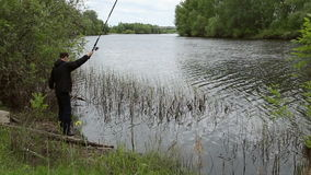 Fisherman is fishing on the river stock footage