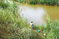 Fisherman is fishing on riverbank Royalty Free Stock Images