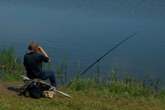 Fisherman with fishing rod catching fish, sitting riverside Royalty Free Stock Image