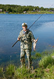 Fisherman with a fishing rod and fish Stock Image