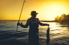 Fisherman with a fishing rod in his hand and a fish caught stands in the water against a beautiful sunset. Royalty Free Stock Image