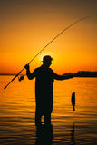 A fisherman with a fishing rod in his hand and a fish caught stands in the water. Against a beautiful sunset Stock Photo