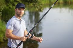 Fisherman with fishing rod on lake shore. Man catches of fish on river. Leisure activity. Hobby in outdoors. Fish hunter. royalty free stock photos