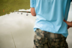 Fisherman with a fishing rod near the pond Royalty Free Stock Photo