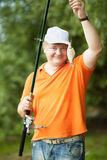 Fisherman. A fisherman with a fishing rod on the river bank Royalty Free Stock Photos