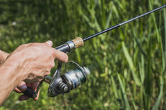 Fisherman with a fishing rod on the river bank. Fisherman start to fishing by spinning on river in sunny weather stock photos