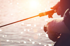 Fisherman with a fishing rod on the river bank. Fisherman start to fishing by spinning on river in sunny weather stock images