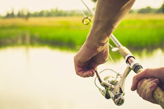 Fisherman with a fishing rod on the river bank. Fisherman start to fishing by spinning on river in sunny weather royalty free stock images