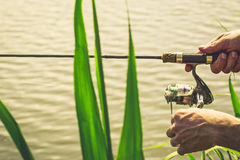 Fisherman with a fishing rod on the river bank. Fisherman start to fishing by spinning on river in sunny weather stock photography