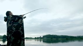 Fisherman fishing with a rod on river bank. Summer fishing stock video