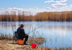 A fisherman with a fishing rod sitting on a chair Stock Photos
