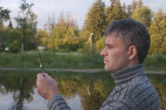 Fisherman. Man with a fishing rod checks tackle Royalty Free Stock Photo