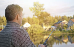 Fisherman. With a fishing rod stands on the shore of lake, sunrise Stock Images