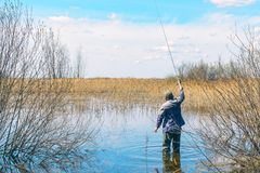 Fisherman with fishing rod stands in the water Royalty Free Stock Image