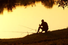 Fisherman with fishing rods in the evening at sunset. Royalty Free Stock Image