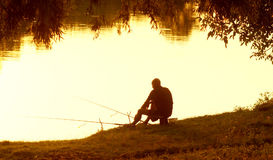 Fisherman with fishing rods in the evening at sunset. Royalty Free Stock Photos