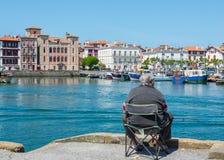 Fisherman fishing in Saint-Jean de Luz - Ciboure harbour. Aquitaine, France. Royalty Free Stock Photos