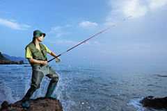 A fisherman fishing at the sea. A fisherman fishing at the Aegean sea Stock Photos
