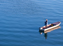 Fisherman fishing in the sea. Fisherman standing on a boat and fishing in sea Royalty Free Stock Images