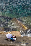 Fisherman is fishing on sea stone, top vertical Royalty Free Stock Images