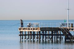 Fisherman fishing with spinning rods, reels at lake water. stock photo