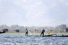 Fishermen at Inle Lake. A fisherman fishing with stilted homes behind them at Inle Lake, Myanmar Stock Image