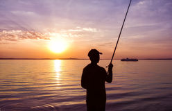Fisherman fishing on sunset Stock Photography