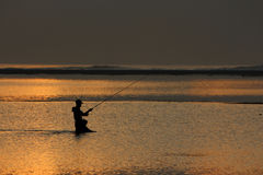 Fisherman Fishing at Sunset or Sunrise. On the sea Stock Images