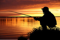 Fisherman with fishing tackle at sunrise. Fisherman with fishing tackle sitting on a coast at sunrise Stock Images