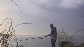 Fisherman on a fishing trip on a lake with a fishing rod in his hand. In the morning hd stock footage