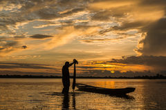Fisherman is fishing by using fishing net on the river. Stock Images