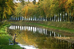 Fisherman is fishing on waterfront in autumn landscape Stock Photo