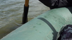 Fisherman floats in a boat rowing with a paddle stock footage