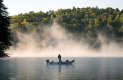 Fisherman in Fog 1. Early morning shot of a fisherman in the rising fog on Lake Burton in north Georgia royalty free stock photography